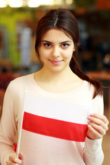 Happy female student holding flag of Poland