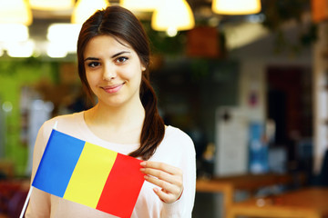 Happy female student holding flag of Romania