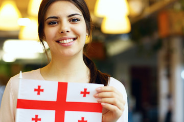 Smiling female student holding flag of Georgia