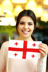 Cheerful female student holding flag of Georgia