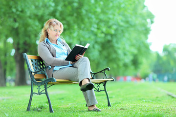 Mature lady relaxing with a book in park