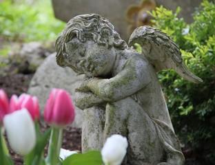 Engel ruht auf Grab im Frühling
