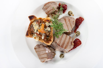 Meat with mushrooms on a white plate