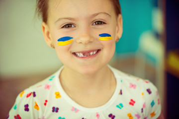 Ukrainian girl with national flag on cheek
