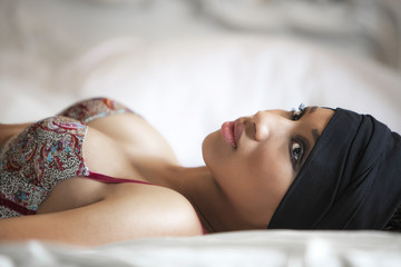 Model lying on a bed and wearing a bra