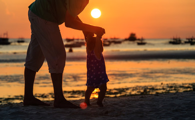 Silhouette of father and daughter on the beach