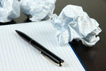 Crumpled paper balls with notebook and pen on wooden background