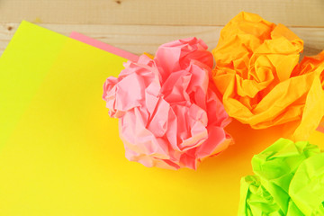 Colorful crumpled paper balls on wooden background