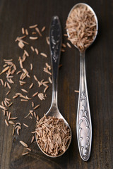 Spice cumin in spoons on wooden background
