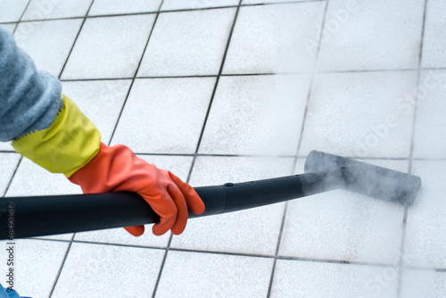 Woman using steam cleaner - 64951632