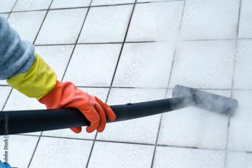Leinwandbild Motiv Woman using steam cleaner