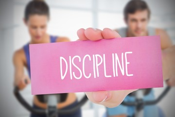 Woman holding pink card saying discipline