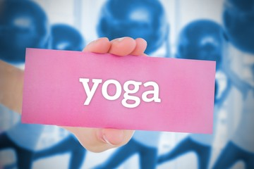 Woman holding pink card saying yoga