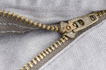 Close up zipper on a pair of grey jeans