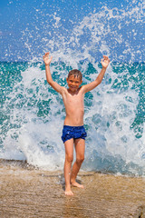 Little boy on the beach with big splashes