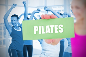 Fit blonde holding card saying pilates