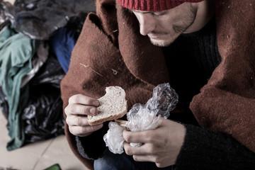 Poor man eating sandwich