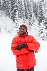 African American Cheerful black man in ski suit in snowy winter