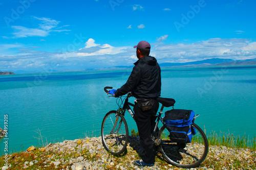 Fotobehang Wielersport göl manzarası izleyen bisikletçi