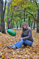 Girl in autumn park with balloon sits on the stump
