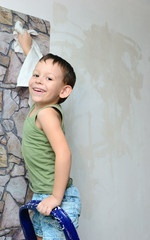 A boy stands on a ladder and glues wallpaper
