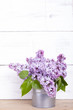 bouquet of lilac flowers on white wooden background