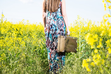 Girl with a suitcase in a field of yellow flowers