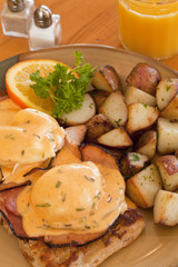 organic eggs benedict with ham and potatoes