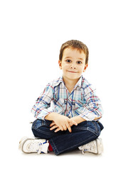 Smiling little boy sitting down on floor in jeans