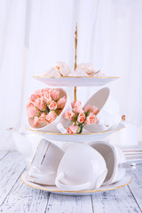 Cups in vase on table on bright background