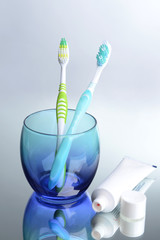 Toothbrushes in glass on light grey background