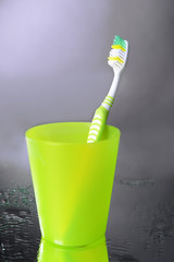 Toothbrush in glass on grey background