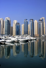 dubai marina with yaghts and residential tower view from bridge