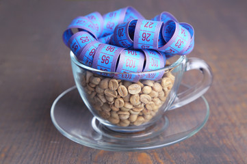 Raw green coffee beans in glass cup and measuring tape,