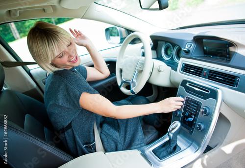 Leinwanddruck Bild attractive woman listen radio in her car