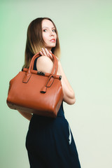 Elegant outfit. Stylish woman with brown bag