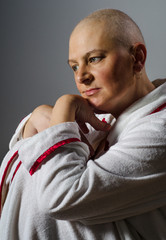 Bald woman suffering from cancer sitting in the chair