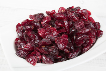 Dried cranberries in a bowl on a white background