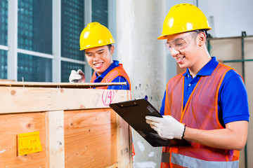Asian construction workers on site open wood box
