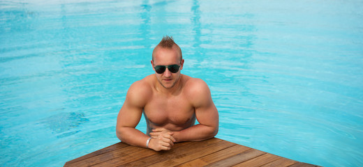 muscular man posing in the swimming pool
