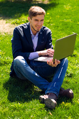 man on the grass. fashion style. talking skype. outdoor