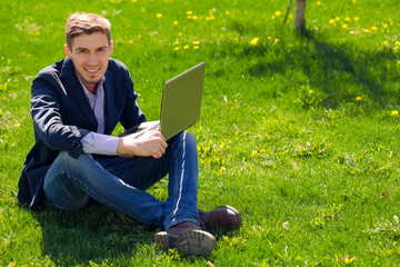 business man on the grass. fashion style. talking skype. outdoor