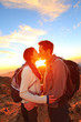 Kissing couple - romantic lovers hiking at sunset
