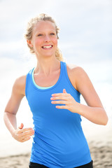 Exercising young woman running and jogging happy