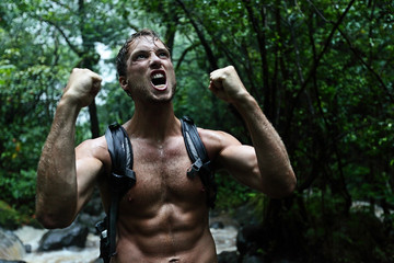 Muscular survivor man in jungle rainforest