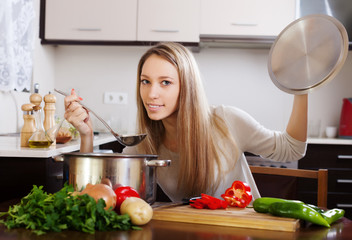 Ordinary blonde woman  with ladle cooking soup