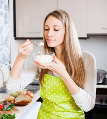 woman in apron eating curd cheese