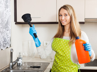 Happy woman with plunger and detergent in kitchen
