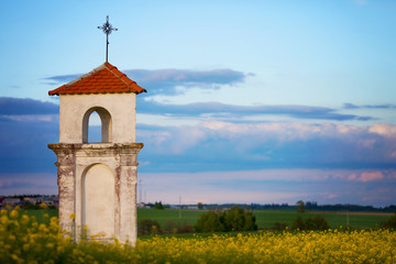 Little chapel in a rape field on sunset