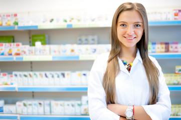 Beautiful blonde pharmacist in drugstore or pharmacy smiling